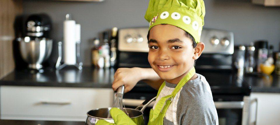Nice little kid in chef hat at kitchen